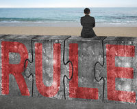 Businessman sitting on huge concrete puzzles with red rule word Royalty Free Stock Photography