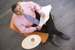 Businessman sitting indoors with coffee and folder Stock Image