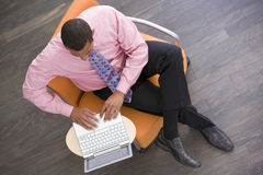 Businessman sitting indoors with laptop Stock Image