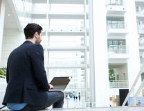 Businessman sitting indoors with laptop Stock Photo