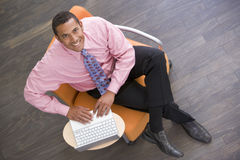 Businessman sitting indoors with laptop smiling Royalty Free Stock Photo