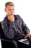 Businessman sitting with laptop and chin resting Royalty Free Stock Photo