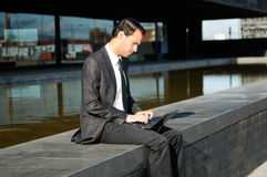 Businessman sitting with a laptop computer Stock Photography