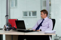 Businessman sitting with laptop at office Royalty Free Stock Photography