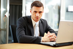 Businessman sitting with laptop at office Royalty Free Stock Image