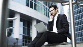 Businessman sitting with a laptop and talking on phone outside stock footage