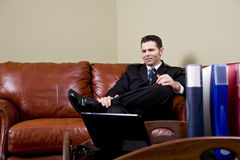 Businessman sitting on leather couch in office Royalty Free Stock Images
