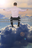Businessman sitting on light metal girder beam over cloud sky in Royalty Free Stock Photography