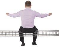 Businessman sitting on light metal girder beam on Royalty Free Stock Image