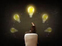 Businessman sitting with lightbulbs over his head Royalty Free Stock Photography