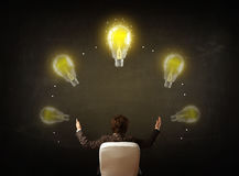 Businessman sitting with lightbulbs over his head Royalty Free Stock Photos