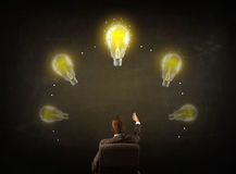 Businessman sitting with lightbulbs over his head Royalty Free Stock Images
