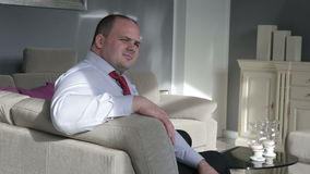 Businessman sitting in living room on couch and looks satisfied stock video