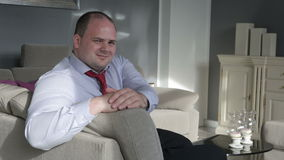 Businessman sitting in living room on couch and smiles and nods at camera stock footage