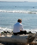 Businessman sitting on a log at the beach. Businessman taking a break at the beach royalty free stock image