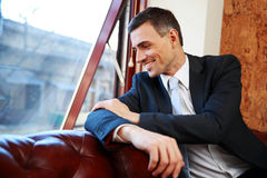 Businessman sitting and looking in window Stock Photos