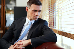Businessman sitting and looking in window Royalty Free Stock Photo