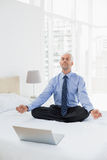 Businessman sitting in lotus pose with laptop on bed Royalty Free Stock Photo