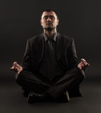 Businessman sitting in lotus position Stock Photos