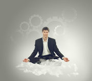 Businessman sitting in lotus position on a cloud. And think mechanical thoughts stock photos