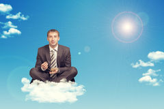 Businessman sitting in lotus position on cloud Stock Photos