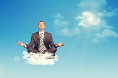 Businessman sitting in lotus position on cloud Royalty Free Stock Photo
