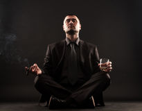Businessman sitting in lotus position,meditateing. Businessman sitting in lotus position trying to meditate while holding cigar and whiskey in hands Stock Photography