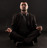Businessman sitting in lotus position,meditateing. Businessman sitting in lotus position trying to meditate while holding cigar and whiskey in hands Royalty Free Stock Photography