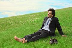Businessman sitting on the meadow barefoot Royalty Free Stock Photos