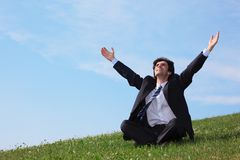 Businessman sitting  on the meadow with hands up Royalty Free Stock Photo