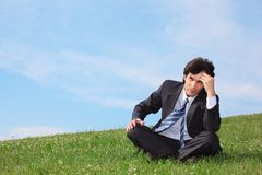 Businessman sitting  on meadow and thinking Royalty Free Stock Image
