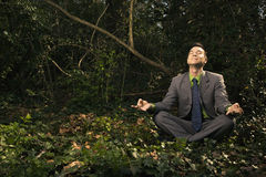Businessman Sitting in Meditation Outside Royalty Free Stock Images