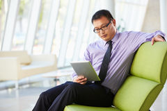 Businessman Sitting In Modern Office Using Digital Tablet Stock Photos