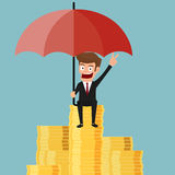 Businessman sitting on money stack holding umbrella protecting his money to investments. Stock Images