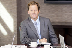 Businessman Sitting in Office Boardroom Royalty Free Stock Image