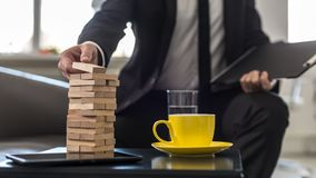 Businessman sitting in office building a tower of stacked blocks. Of wood with yellow cup and tablet on table stock photos