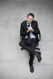 Businessman sitting on an office chair. Against concrete floor background Royalty Free Stock Photography