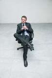 Businessman sitting on an office chair. Against concrete floor background Royalty Free Stock Images