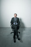 Businessman sitting on an office chair. Against concrete floor background Stock Images
