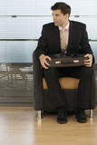 Businessman sitting in office chair, briefcase in lap Stock Image