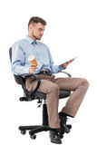 Businessman sitting in a office chair and drinking coffee Stock Images