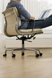 Businessman sitting in office chair with feet up on desk, using laptop, profile, surface level Royalty Free Stock Photo