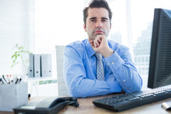Businessman sitting on an office chair with hand on chin Royalty Free Stock Images