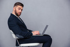 Businessman sitting on the office chair with laptop Stock Photos