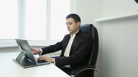 Businessman sitting in an office chair at the table and typing on the silver laptop. A young man in a white shirt and jacket working on notebook stock footage