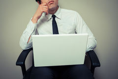 Businessman sitting in office chair and thinking. A young businessman is sitting in an office chair with his laptop and is thinking Stock Images