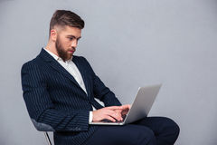 Businessman sitting on office chair and using laptop Stock Image
