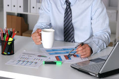 Businessman sitting at office desk having a coffee break Royalty Free Stock Photos