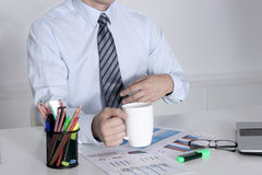 Businessman sitting at office desk having a coffee break Stock Photos