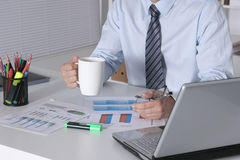 Businessman sitting at office desk having a coffee break Stock Images
